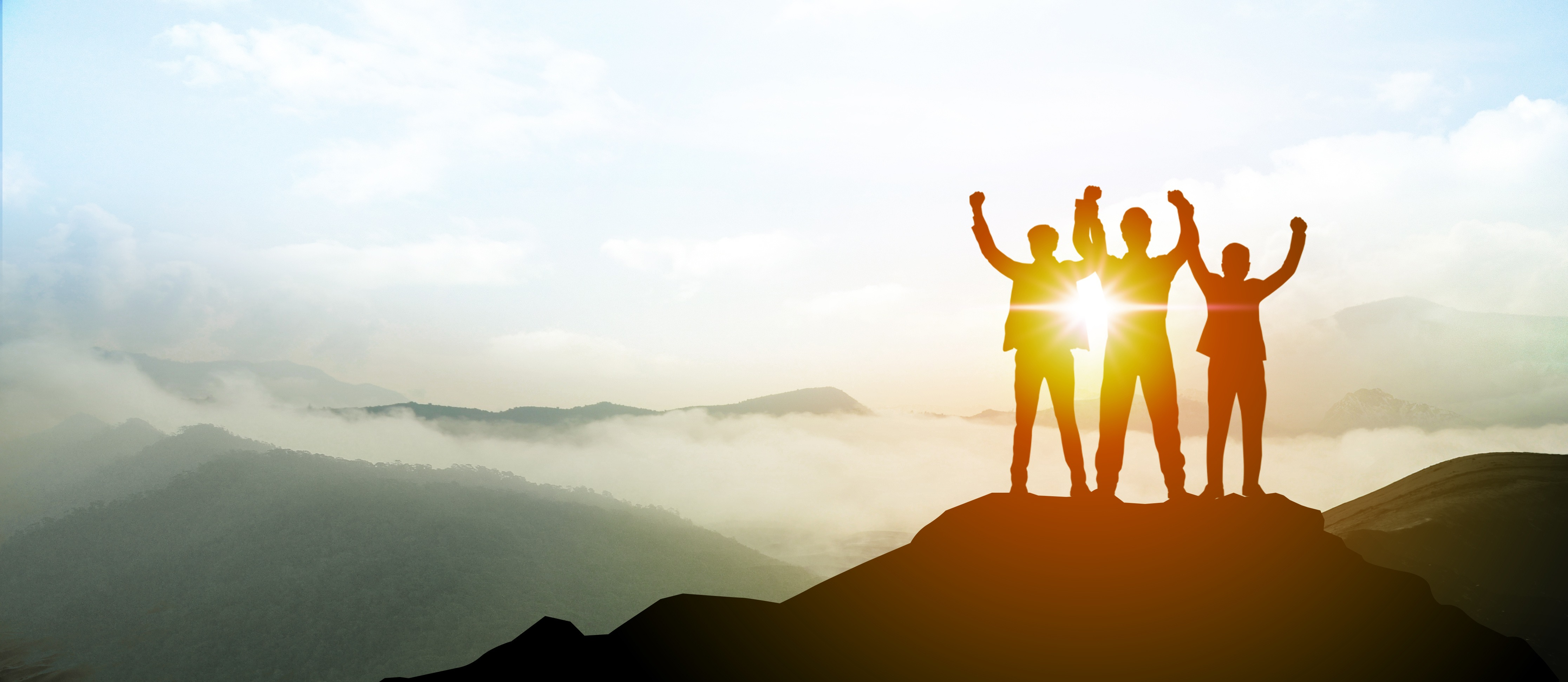 Team of 3 on top of a hill with the sun in background