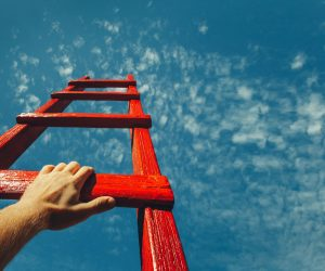 Red ladder with hand going towards the sky